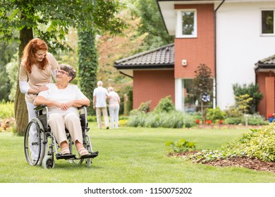 Nurse supporting disabled senior woman in a wheelchair in the garden