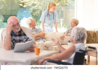 Nurse supporting elderly people during daily activities in nursing house