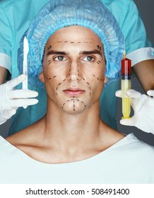 Nurse with syringe and scalpel near the face of scared patient. Attractive man with pencil surgical lines (forehead, eyes, nose, cheekbone and jaw). Plastic Surgery concept