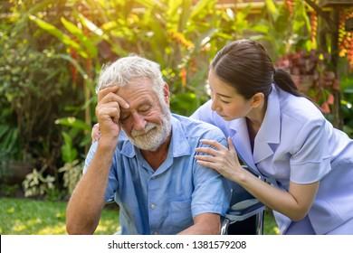 Nurse take care and comfort depressed thoughtful elderly man on wheelchair in garden at nursing home