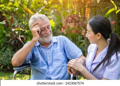Nurse take care and comfort elderly man on wheelchair in garden at nursing home