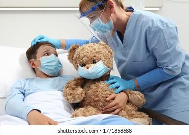 Die Krankenschwester kümmert sich um das Kind im Krankenhausbett, das mit Teddybären spielt, Schutzmasken trägt, das Schutzkonzept Corona-Virus covid 19,