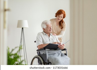 Nurse taking care of a man in a wheelchair in a nursing home