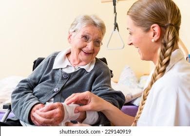 Nurse taking care of senior woman in retirement home bandaging a wound