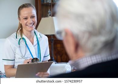 Nurse Taking Medical Notes From Senior Man At Home On Visit