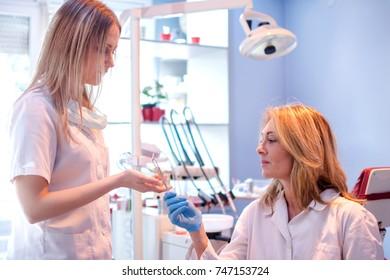 Nurse taking medical tools from female dentist in dental office.