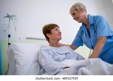 Nurse talking to a senior patient in hospital room
