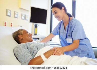 Nurse Talking To Senior Woman In Hospital Room