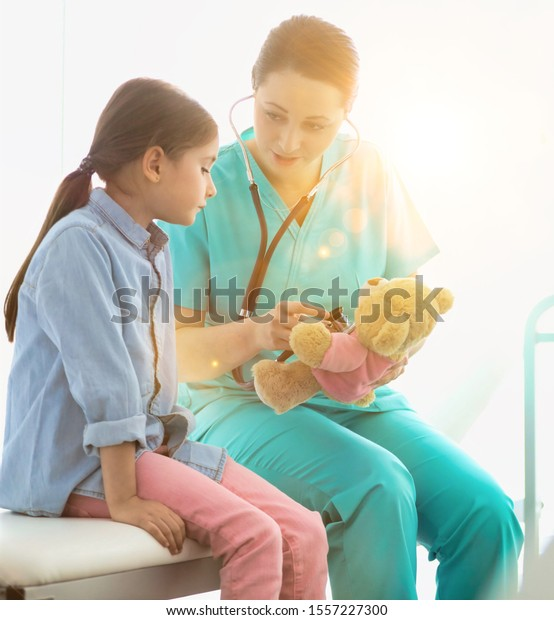 Nurse teaching child patient how to check heartbeat with teddy bear at hospital with yellow lens flare in background