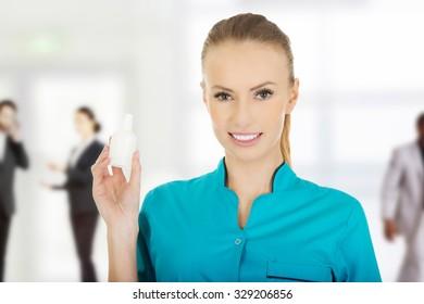 Nurse in uniform holding hydrogen peroxide.