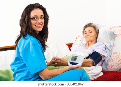 Nurse using digital blood pressure for senior patient.