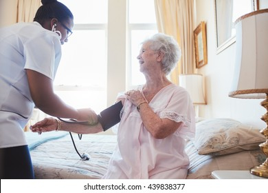 Nurse visiting senior female patient at home and taking blood pressure. Old woman sitting on bed.