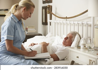 Nurse Visiting Senior Male Patient In Bed At Home