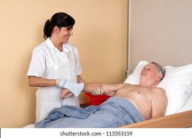 a nurse washes a patient