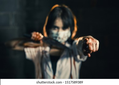 Nurse woman assassins with blood holding a knife in his hand in a dark room Point your finger forward, zombie horror lady. Halloween dressing concept.