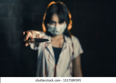 Nurse woman assassins with blood holding a knife point forward in his hand in a dark room Point your finger forward, zombie horror lady. Halloween dressing concept.