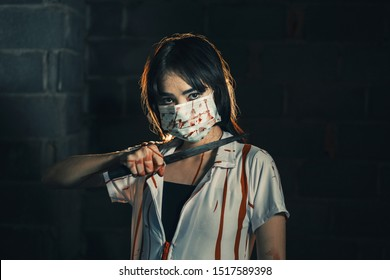 Nurse woman assassins with blood holding a knife in his hand in a dark room, zombie horror lady. Halloween dressing concept.