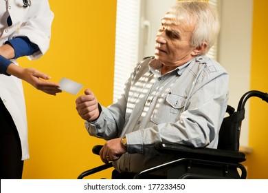 Nurse woman giving client's card to senior man in wheelchair