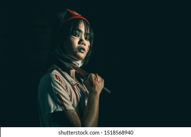 Nurse woman psychosis holding a bloody knife in hand in a dark room. Zombie horror lady. Halloween dressing concept.
