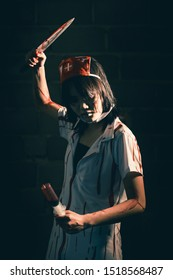 Nurse woman psychosis holding a syringe and a bloody knife in hand in a dark room. Zombie horror lady. Halloween dressing concept.