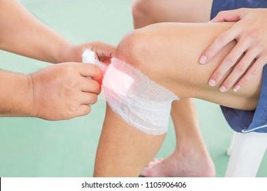 Nurse wounding bandage around knee of patient