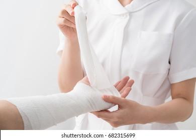 A nurse wrapping a bandage, arm, patient