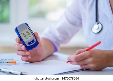 Nurse write blood glucose level of diabetic patient from glucose meter during medical consultation and examination in hospital. Diabetic lifestyle and healthcare