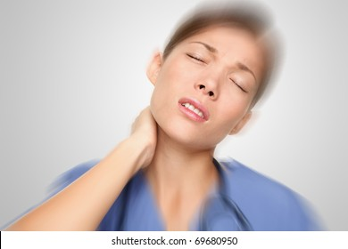 Nurse or young woman doctor having neck and back pain problems at work. Mixed-race Asian / Caucasian female model.