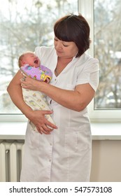 Nurse-midwife with a newborn baby in her arms