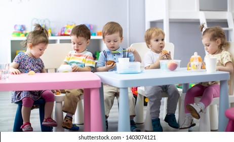 Nursery babies eating food. Kids have lunch in day care or kindergarten
