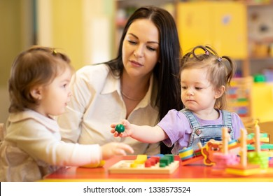Nursery babies group playing with teacher in daycare centre playroom