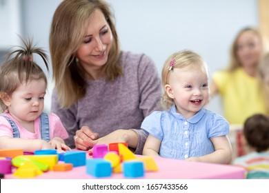 Nursery babies play with teacher in daycare
