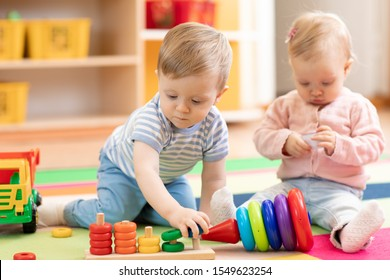 Nursery babies playing with educational toys in creche, early learning