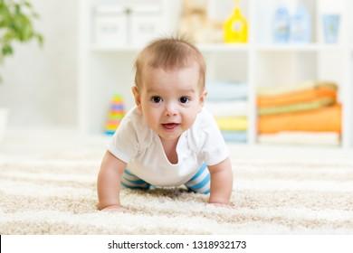 Nursery baby boy crawling on floor indoors at home