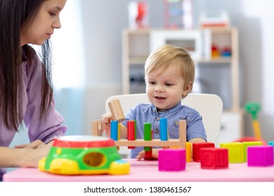 Nursery baby and caregiver play with montessori toys at table in daycare centre
