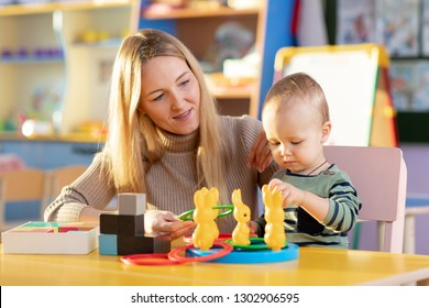 Nursery baby and carer play at table in daycare centre