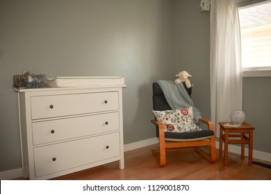 Nursery with chair, toys, dresser, change table and comfort