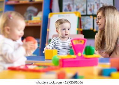 Nursery children play with teacher in kindergarten