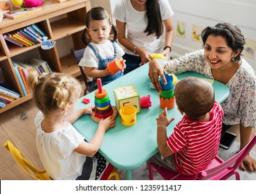 Nursery children playing with teacher in the classroom