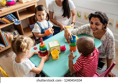 Enfants en maternelle jouant avec un professeur dans la salle de classe
