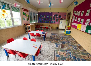In a nursery class with tables and small red chairs for children