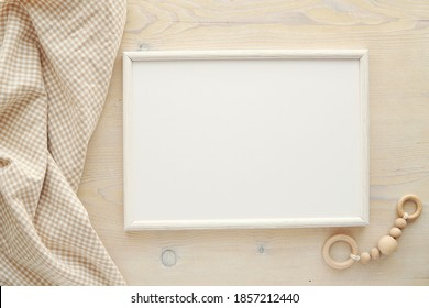 Nursery frame mockup, horizontal white wooden frame mock up for baby room art, pregnancy announcement, top view, flat lay. - Shutterstock ID 1857212440