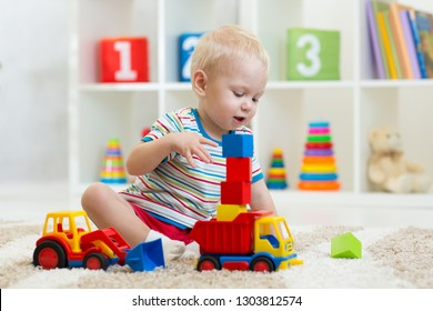 nursery kid boy toddler playing with toys in kindergarten