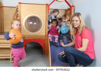A Nursery nurse with 4 Kids on a indoor slide