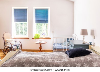 A nursery room interior with a bed for adults, a white cot for a child an a rocking chair. Windows with blinds in the background. Real photo.