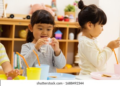 Nursery school children are eating snacks