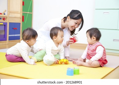 Nursery school children and nursery playing with toys