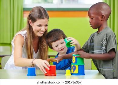 Nursery teacher building tower with children in a kindergarten