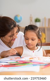 Nursery teacher helping little girl painting with watercolors