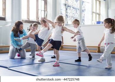 Nursery teacher helping one of her students during a physical education lesson.